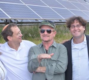 Yosef Abramowitz and Chaim Motzen at the Rwanda field with superstar Bono